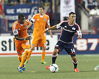 New England Revolution midfielder Diego Fagundez (14) looks to pass as Houston Dynamo defender Kofi Sarkodie (8) closes. In a Major League Soccer (MLS) match, Houston Dynamo (orange) defeated the New England Revolution (blue), 2-1, at Gillette Stadium on July 13, 2013.