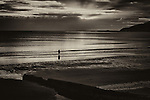 A small lonely figure on at the seashore at dusk in Dorset England