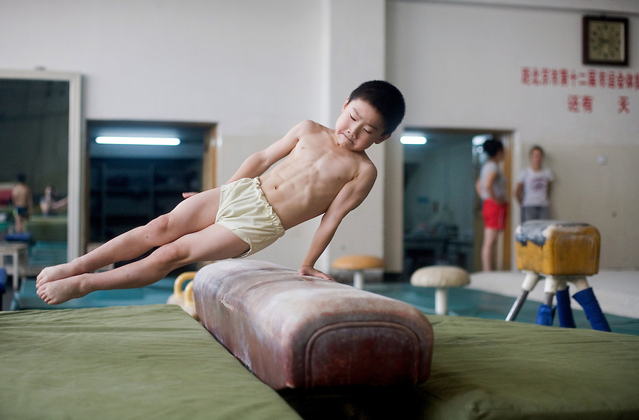 Eight year old Zhang Yu trains on the pummel horse at a sports school to train gymnasts in Beijing.