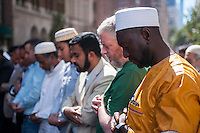 Muslims from the tri-state pray on Madison Avenue  in New York on Sunday, September 25, 2016 prior to the American Muslim Parade. The annual parade, now in it's 31st year, celebrates the diversity and heritage of Islamic culture. Participants march down Madison Avenue ending in a street fair. (© Richard B. Levine)