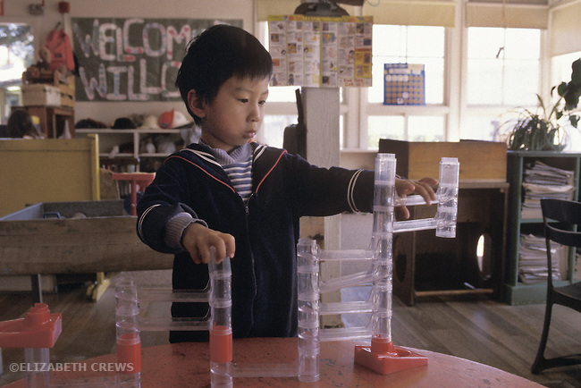 Berkeley, CA Asian boy, three years old, in solitary play with marble track toy at preschool