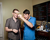Bartenders Alex Flynn, left, and Josh Bryant discuss a new drink made with sub-standard vodka.