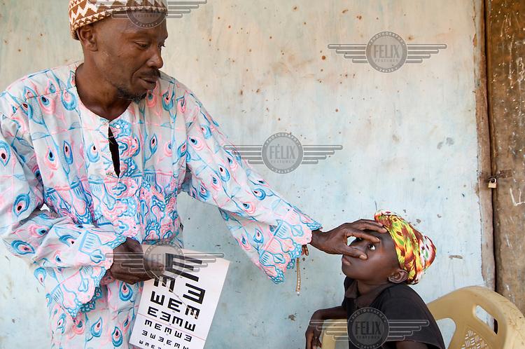 Alagie Touray, head of the Association of Nyatero (Friends of the Eye), examines the eyes of Fatouma Banda in Kafuta village.