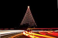 Cars light streaks whizzing past the illuminated Zilker Park Christmas Tree