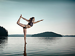 Young woman practicing Hatha yoga on a floating platform in water on the lake during sunrise in the morning. Yoga Dancer posture, Dandayamana Dhanurasana. Muskoka, Ontario, Canada.