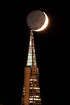 A waxing moon seems to touch the Transamerica Pyramid in San Francisco as it moves through a fogless evening. The photo was taken from Treasure Island as the sun was setting over San Francisco, California.