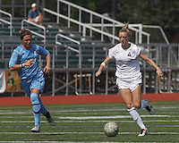 Boston Aztec forward Lucy Gildein (27) brings the ball forward as Seacoast United Mariners defender Morgan Libby (22) closes. In a Women's Premier Soccer League (WPSL) match, Boston Aztec (white) defeated Seacoast United Mariners (blue), 2-1, at North Reading High School Stadium on Arthur J. Kenney Athletic Field on on June 23, 2013. Due to injuries through the season, Seacoast United Mariners could only field 10 players.
