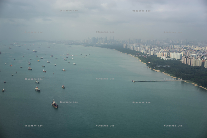Ships line the coast as the morning fogginess lifts from a groggy Singapore cityscape. What does the future of cities look like? I explore Singapore and its continuous vertical development as it tries to balance the urban cityscape of sky scrapers with artificial nature by installing vast green walls. Photo by Suzanne Lee
