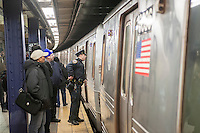 An NYPD officer during an investigation in the Times Square station in New York on Wednesday, March 2, 2016. The NYPD announced an effort to combat a spike in crimes, particularly slashings, in the subway by having more officers on trains and platforms. An officer will be on every train from 8 PM to 4 AM, a plan that was used years ago. Crime in the subway is up 25% compared to last year. (© Richard B. Levine)
