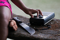 Wounaan woman tuning in her radio by the river. Biroquera, Darien, Panama.