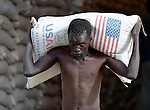 A man unloads sorghum for displaced families in Agok, a town in the contested Abyei region where tens of thousands of people fled in 2011 after an attack by soldiers and militias from the northern Republic of Sudan on most parts of Abyei. Although the 2005 Comprehensive Peace Agreement called for residents of Abyei--which sits on the border between Sudan and South Sudan--to hold a referendum on whether they wanted to align with the north or the newly independent South Sudan, the government in Khartoum and northern-backed Misseriya nomads, excluded from voting as they only live part of the year in Abyei, blocked the vote and attacked the majority Dinka Ngok population. The African Union has proposed a new peace plan, including a referendum to be held in October 2013, but it has been rejected by the Misseriya and Khartoum. The Catholic parish of Abyei, with support from Caritas South Sudan and other international church partners, has maintained its pastoral presence among the displaced and assisted them with food, shelter, and other relief supplies. The sorghum being unloaded here, a donation by the U.S. government, is part of an aid distribution by the World Food Programme.