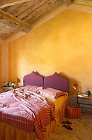 White borders around the yellow walls emphasise the shape of this bedroom