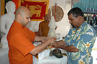 Reverend Dhaampi from the Pasadena Buddhist  Temple blesses Chanra de Silva during Sri Lanka Day at Third Street Promenade on Saturday, Aug 06, 2011..