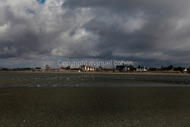 Low angle view of Le Crotoy beach and village, Baie de Somme, France, pictured on February 20, 2010 at midday.  Le Crotoy is said to be the only South facing beach in Northern France. Beneath wide skies the channels of seawater snake across the open sands creating natural abstract patterns. Picture by Manuel Cohen.
