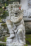 Ubud, Bali, Indonesia; stone statues line the entrance stairs of the Tjampuhan Temple on an overcast early morning