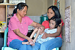 In Abucay, a seaside town in the Philippines province of Bataan, Estrellita Guanzon, a health worker, carries out therapy with Raisa Valencia, ho has cerebral palsy, as her mother Mayra holds the 8-year old girl. The girl's family is part of the local Persons with Disabilities (PWD) organization.