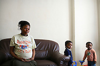 """20 year old Thania, from DR Congo, with her two children born after she was forced into prostitution, in the bedsit where she now stays. She arrived in the UK in September 2004 claiming asylum after her family were murdered by Congolese soldiers. She was forced to watch her brother burned to death after a tyre was set alight around his neck. She was raped but managed to escape. After her claim was refused she walked the streets begging people for food and money, """"I couldn't think properly because I was so hungry."""" Thania is one of an estimated 300,000 rejected asylum seekers living in the UK. ."""