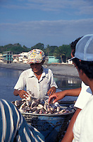 Boy selling fresh fish on the town pier in La Libertad, El Salvador