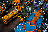 Decorated graves, covered by cempasúchil flowers (marigolds), are seen during the Day of the Dead celebration at the cemetery in Tzintzuntzan, Michoacán, Mexico, 2 November 2014. Day of the Dead ('Día de Muertos') is a syncretic religious holiday, celebrated throughout Mexico, combining the death veneration rituals of the ancient Aztec culture with the Catholic practice. Based on the belief that the souls of the departed may come back to this world on that day, people gather on the gravesites praying, drinking and playing music, to joyfully remember friends or family members who have died and to support their souls on the spiritual journey.