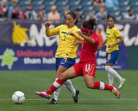 Brazilian defender Daiane (4) and Canadian midfielder Desiree Scott (11) battle at midfield. In an international friendly, Canada defeated Brasil, 2-1, at Gillette Stadium on March 24, 2012.