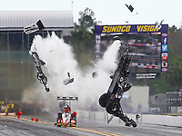 Mar 14, 2015; Gainesville, FL, USA; NHRA top fuel dragster driver Larry Dixon (right) crashes and goes airborne alongside Doug Kalitta after his car broke in half during qualifying for the Gatornationals at Auto Plus Raceway at Gainesville. Dixon walked away from the incident. Mandatory Credit: Mark J. Rebilas-