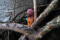 A Colombian girl stands behind the branch of a tree while searching for shellfish in the mangrove swamps on the Pacific coast, Colombia, 12 June 2010. Deep in the impenetrable labyrinth of mangrove swamps on the Pacific seashore, hundreds of people struggle everyday, searching and gathering a tiny shellfish called 'piangua'. Wading through sticky mud among the mangrove tree roots, facing the clouds of mosquitos, they pick up mussels hidden deep in mud, no matter of unbearable tropical heat or strong rain. Although the shellfish pickers, mostly Afro-Colombians displaced by the Colombian armed conflict, take a high risk (malaria, poisonous bites,...), their salary is very low and keeps them living in extreme poverty.