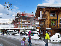Switzerland. Canton Valais. Verbier is a village located in the municipality of Bagnes. The village lies on a south orientated terrace at around 1,500 metres. The terrace lies on the east side of the Val de Bagnes. Shopping and Christmas decoration. Three young girls cross the street.  Alpine wooden chalet with a sign for the ski school ( ecole de ski La Fantastique). Construction. Verbier had 3000 permanent residents in 2010. The number of residents can rise to 35,000 in the winter season. Verbier is one of the largest holiday resort and ski areas in the Swiss Alps. 4.01.2012 © 2012 Didier Ruef