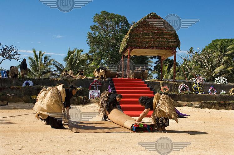Mourners wearing ta'ovala (a traditional pandanas mat worn on formal occasions) preparing mats for the burial service at the Namoala royal tombs during the royal funeral of HRH Prince Tu'ipelehake (Uluvalu Ngu Takeivulai) and HRH Princess Kaimana Hauoli 'o Kuini Tu'ipelehake. The royals died following a car crash in California on 5th July 2006.