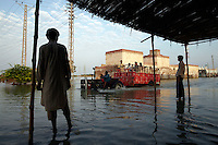 Men look on as a tractor ferries people through the floodwaters in the village of Sultan Kot. Severe flooding had left at least 1,600 people dead and affected up to 20 million.