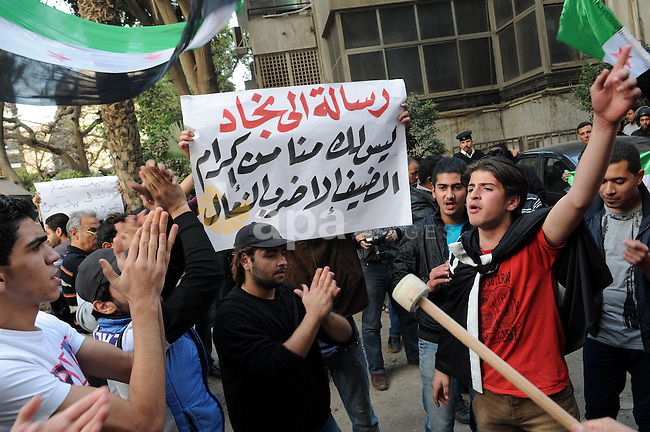 Protesters wave the pre-Baath Syrian flag, now used by the Free Syrian Army, as they shout slogans against the Syrian and Iranian regimes during a demonstration outside the Iranian embassy in the Egyptian capital Cairo on February 6, 2013. Egyptian President Mohamed Morsi urged Syrian opposition groups to unify, as he addressed leaders of Islamic states at a summit of the Organisation of Islamic Cooperation in Cairo. Iran is the chief regional backer of Syrian President Bashar al-Assad, while Egypt and Gulf powerhouse Saudi Arabia bitterly oppose Assad and support rebels seeking his ouster. Photo by Ahmed Asad