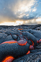 The sun sets behind glowing, textured lava in the expansive fields of Hawai'i Volcanoes National Park, Hawai'i Island.
