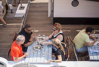 Diners enjoy drinks and oysters aboard the Grand Banks restaurant on the schooner Sherman Zwicker docked in Hudson River Park in New York on Saturday, July 12, 2014. The ship will be docking at Pier 25 on a trial run until the end of October pending community board approval. (© Richard B. Levine)