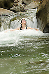 Woman relaxing in a small waterfall on Hanakapi'ai Stream, Kauai, Hawaii