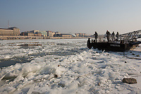 People watch ice blocks floating on river Danube in Budapest, Hungary on January 10, 2017. ATTILA VOLGYI