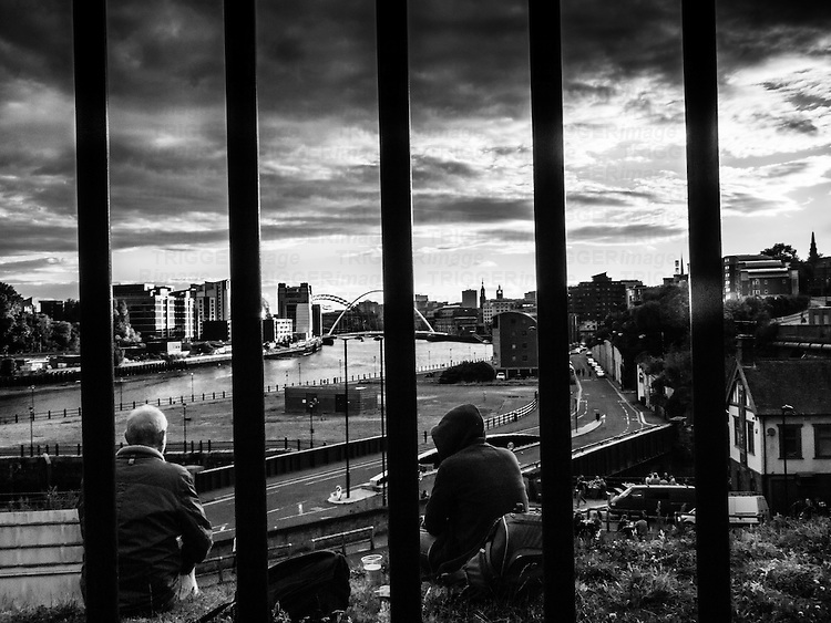 Figures watch the river in Newcastle