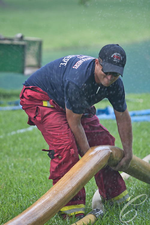 A South Montgomery County firefighter unkinks an intake hose as it draws water from the Laitkep's pond.
