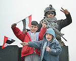Children wave Iraqi flags to celebrate the partial liberation of their city as they climb on top of armored military vehicles in Mosul, Iraq, on January 27, 2017. The Iraqi army, including elite counter-terror commandos, drove the Islamic State group out of the eastern part of the city in early in 2017. Despite the city's new freedom, Christians are unlikely to return soon due to concerns about their security in the largely Sunni Muslim community.