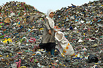 A girl works in the public dump in Manila. Thousands of children work in this dump, recycling materials for a few cents per day.