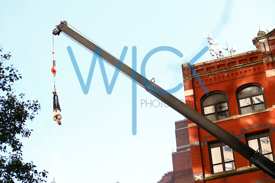 Lee Terbosic performs near the intersection of Wood Street and Liberty Avenue as he attempts to escape from a straight jacket while hanging upside down in Pittsburgh, Pennsylvania on Sunday November 6, 2016. The stunt comes 100 years to the day after Harry Houdini did it himself in the same location. (Photo by Jared Wickerham/Wick Photography)