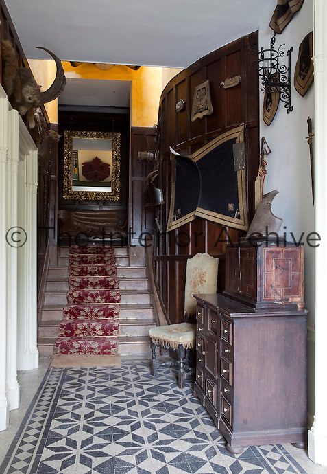A shallow wooden staircase leads from the tiled entrance hall past panelled walls decorated with hunting trophies