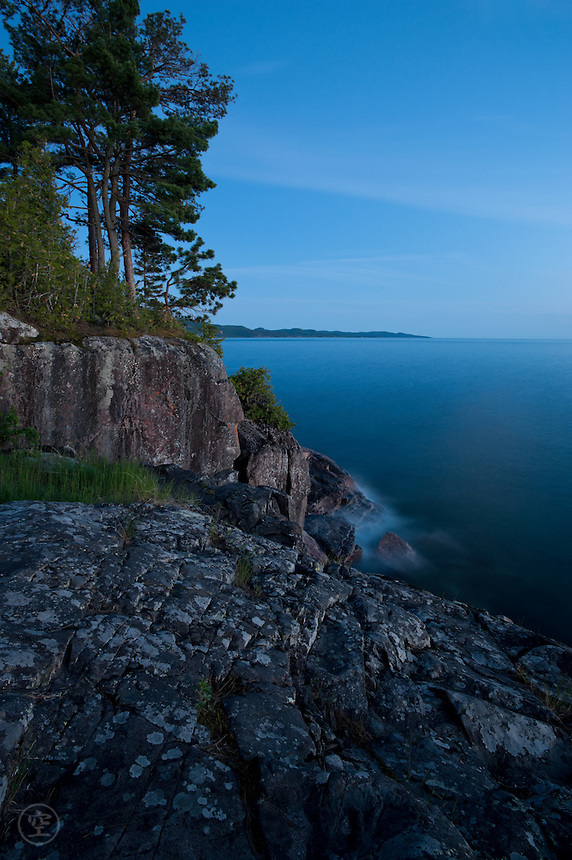 Moonrise at dusk, Lake Superior, Ontario. Pine trees and granite against the blue lake and blue sky, Lake Superior Provincial Park, Ontario, Canada.
