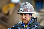A miner outside a mine in Potosi, Bolivia. The mine produces silver and other metals. The man is chewing coca leaves, producing the lump in his cheek.