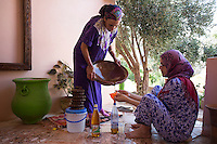Morocco - Tidzi - Saadia Tighanimine (left) pouring the argan oil into a bottle. Most oil will be sold on the international market but some of it is kept for their own consumption and sometimes sold at the market in Tidzi.
