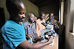 Kasongo Wungudi instructs students in how to use the microscope in the lab of the United Methodist hospital in the Congolese village of Tunda.