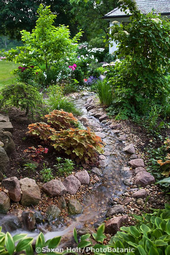 Stream running through backyard garden toward home