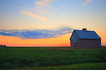 A colorful sun sets over the plains of north central Illinois as a lone bank of clouds floats by. An old red barn sits in the foreground.