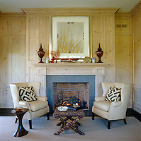 Pine panelling and a woollen rug create a cosy atmosphere in this snug where a log fire is flanked by a pair of comfortable wing-backed leather armchairs
