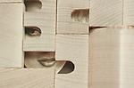 A hidden womans face behind wooden blocks