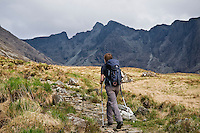 Female hiker hikes on stone path from Glenbrittle leading to Black Cuillins, Isle of Skye, Scotland