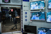 A pedestrian walks as the India-Pakistan cricket match displayed on multi TV screens inside an electronics store in Lenin Sarani in Kolkata, West Bengal, India.